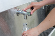 Refilling A Plastic Water Bottle From A Tap Outdoors At The Public Park
