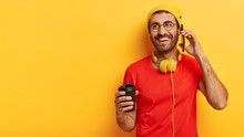 Indoor Shot Of Cheerful Millennial Man Speaks On Mobile Phone, Looks Away, Holds Takeout Coffee Makes Call To Friend Dressed In Stylish Yellow Hat Red T Shirt, Enjoys Spare Time. People, Communication