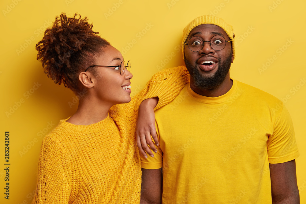 Fototapety, obrazy: Two black friends in yellow clothes, have joyful looks, African American woman leans on shoulder of bearded guy, listens awesome funny story, have fun together, pose in studio. Emotions, relationship
