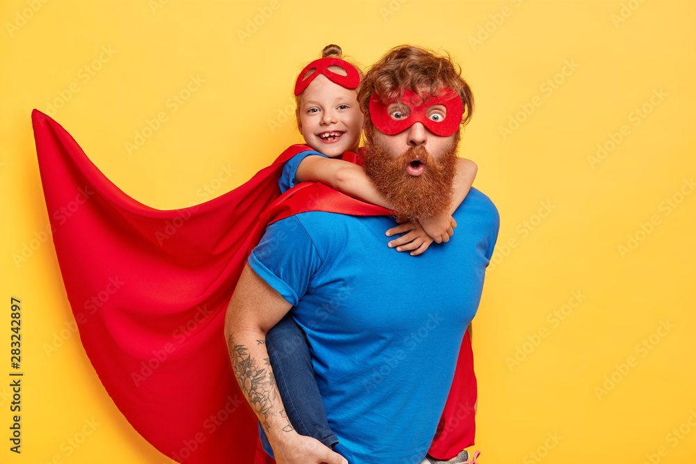 Fototapety, obrazy: Superheroes team ready to save our world. Little kid girl rides back of her father superhero, pretend flying, wears red cape, special mask, isolated on yellow background. Success, motivation, win