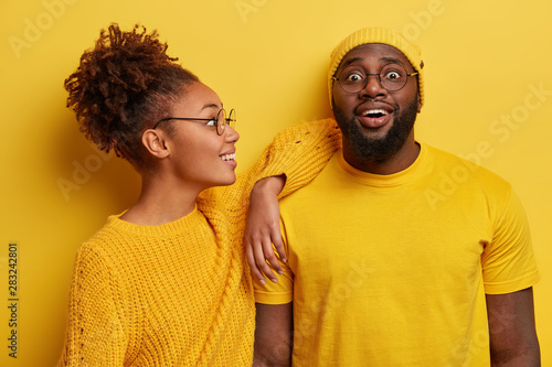 Fotografie, Obraz  Two black friends in yellow clothes, have joyful looks, African American woman leans on shoulder of bearded guy, listens awesome funny story, have fun together, pose in studio