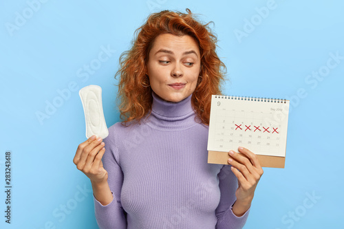 Fotografia  Photo of young woman looks at period calendar, checks menstruation days, holds s