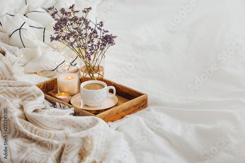 Fotografia, Obraz  Wooden tray of coffee and candles with flowers on bed