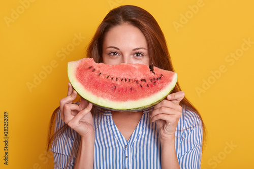 Image of young adorable lady dressed stylish striped shirt, holding piece of watermelon in hands, female hiding behind watermalon and looking directly at camera. People and summertime concept. - 283252819
