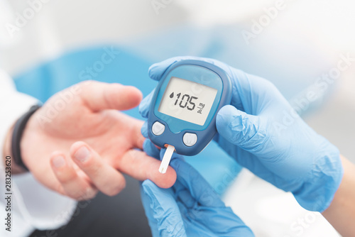 Fotografía Doctor checking blood sugar level with glucometer