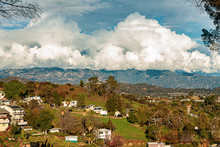 Hillside Homes Mountain Range With Huge Cumulus Nimbus Clouds