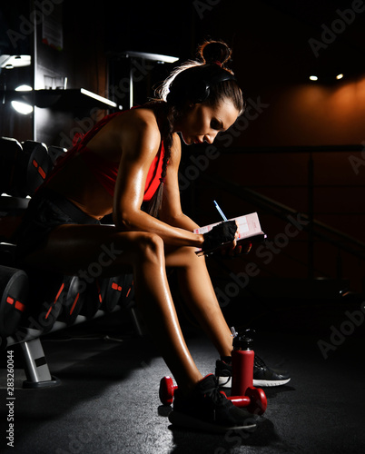 Sporty woman fitness trainer is writing down results in dairy planning practice. Diet and weight loss concept Wall mural