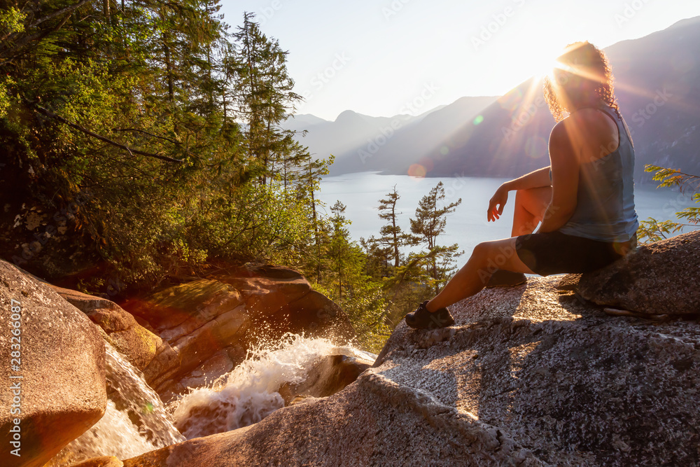 Fototapety, obrazy: Adventurous Girl is sitting on top of a Beautiful Waterfall, Shannon Falls, and watching the sunset. Taken near Squamish, North of Vancouver, British Columbia, Canada.