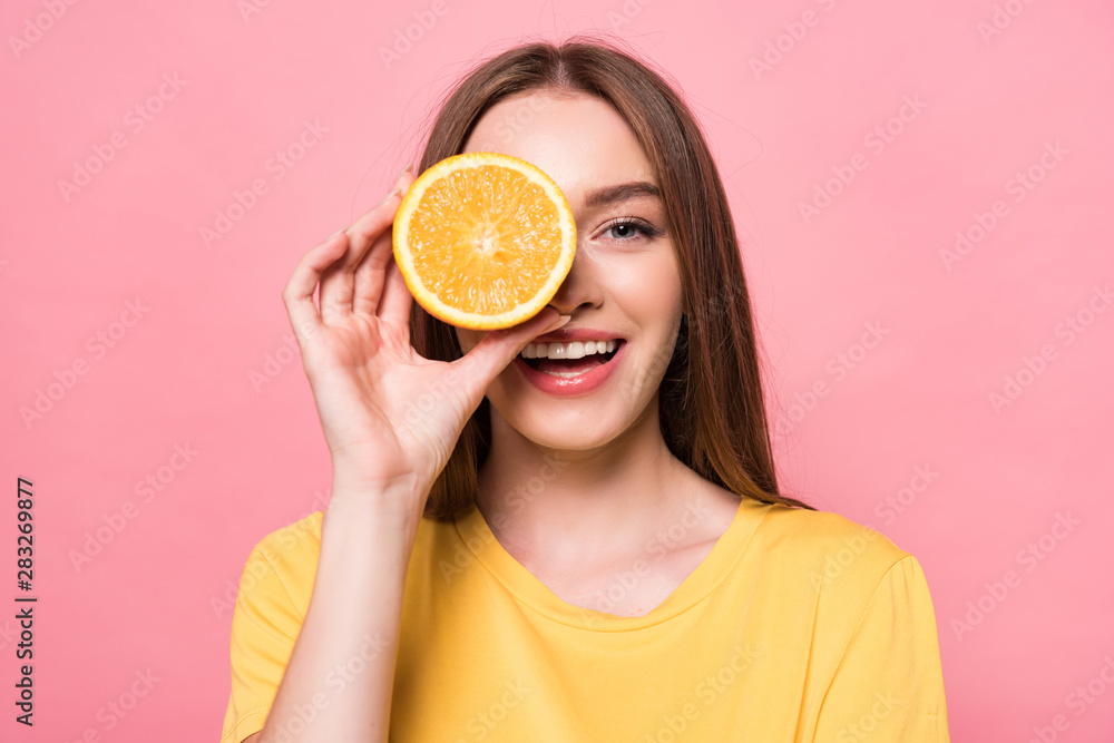 Fototapeta front view of smiling attractive girl holding cut orange isolated on pink