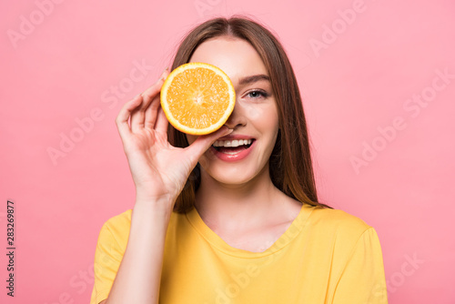 front view of smiling attractive girl holding cut orange isolated on pink Canvas Print