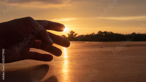 A silhouette of a human hand reaching out gently trying to touch the sun during a beautiful yellow orange sunset during golden hour admiring gods gift to the world Canvas-taulu