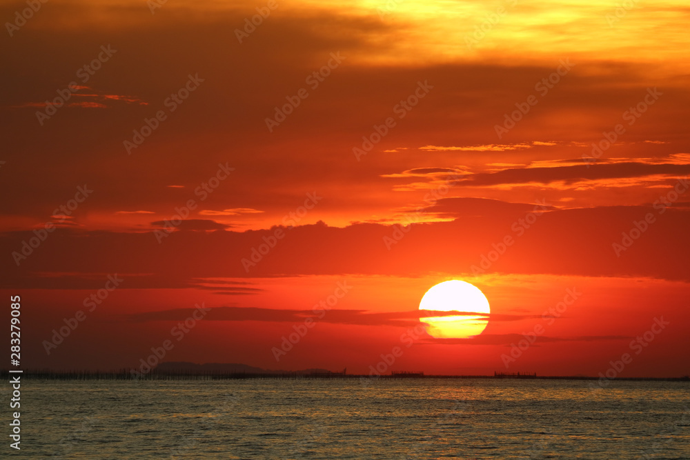 Fototapeta sunset on red yellow sky back soft evening cloud over horizon sea