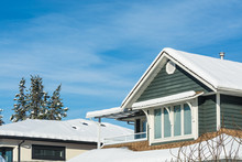 Top Of Residential House In Snow On Sunny Winter Day In Canada.