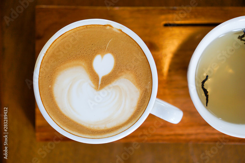 Fotobehang Chocolade Heart-shaped coffee on a brown wood table