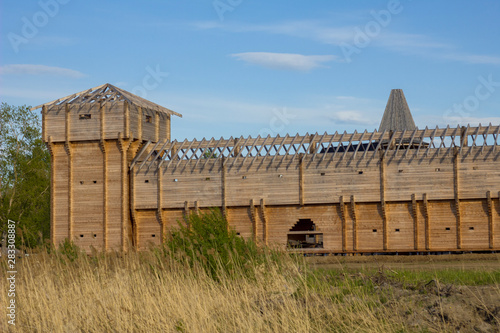 Photo reconstruction of the high wall of an ancient wooden fortress with a tower