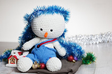 Сrocheted Soft Toy Snowman In Blue Pants On Table,close-up,space For Text.Celebrating Christmas - Winter Concept