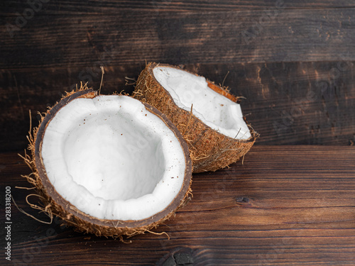 Poster Pays d Asie Two halves of fresh coconut on a dark wooden background. Copy space.