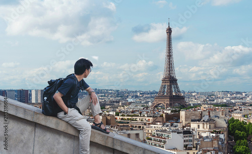 Foto auf Gartenposter Paris a man with backpack looking at Eiffel tower, famous landmark and travel destination in Paris, France