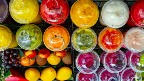 A wide selection of blended, frozen fruit smoothies made from organic grown fruits and juices and served in recycled plastic containers - 283341653