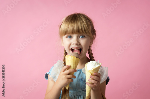 Poster Kruidenierswinkel little girl with pigtails in a blue dress eating ice cream in a cone on a pink background