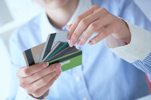 Woman Hand Holding Various Credit Cards And Making Choice With Another Hand Close-up.