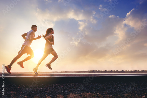 Fototapeta Young couples running sprinting on road. Fit runner fitness runner during outdoor workout with sunset background obraz