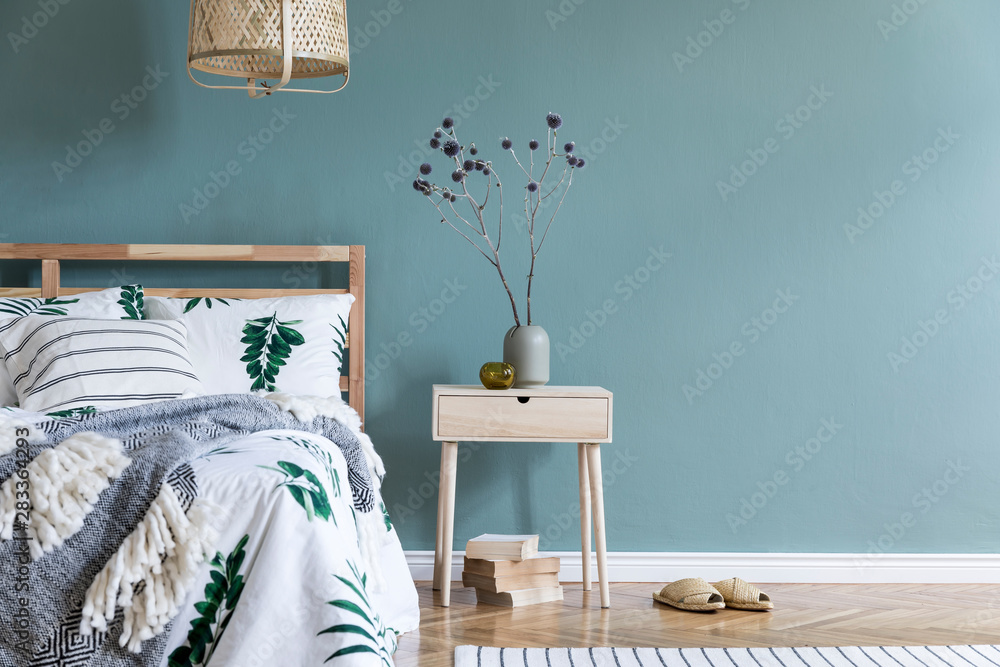 Fototapeta Minimalistic composition of bedroom interior with wooden bed, shelf, flowers in vase, rattan lamp, books and elegant accessories. Beautiful bed sheets, blanket and pillow. Template. Design home decor
