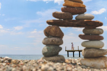 Young Woman Walking On Pier Shown Between A Pebble Tower On The Beach At Assos, Canakkale Of Aegean Sea In Turkey. (Selective Focus)