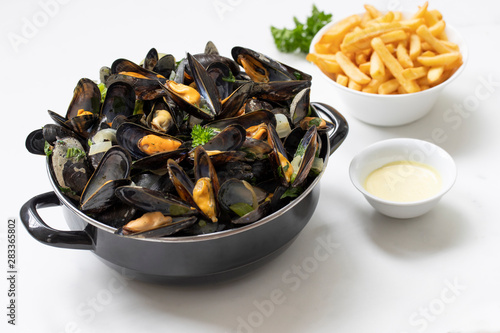 Belgian mussels with potato fries and sauce on white marble table Fototapet