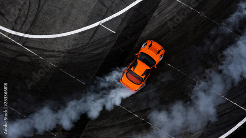 Cuadros en Lienzo  Aerial top view car drifting on asphalt race track with lots of smoke from burning tires