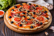 canvas print picture - Pizza with tomato, olives, champignons, ham and cheese on round wooden plate