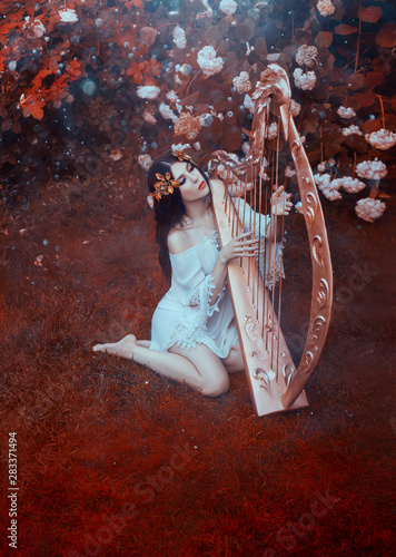 Fotografija A young woman in a white vintage short dress sits on a forest lawn and plays the golden harp glorifying the Lord