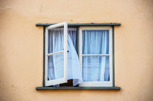 Open Casement Window In Old Stucco House With White Gauze Sheer Curtains Blowing Out Of Them - Close-up