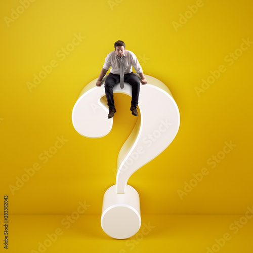 Fotografija  Man sitting on top of a big white question mark on a yellow background