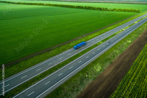 Foto auf AluDibond Grun blue truck on the higthway sunset. cargo delivery driving on asphalt road along the green fields. seen from the air. Aerial view landscape. drone
