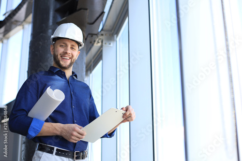 Photo Shot of smiling male architect wearing hardhat and inspecting new building