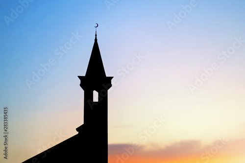 dark silhouette of a muslim mosque with a crescent on the spire at sunset Fototapeta