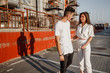 Young stylish guy and girl are standing in the street on the background of urban building in the warm day