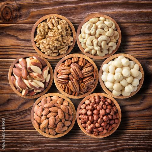 obraz lub plakat various nuts in wooden bowls, top view. food background: pecan, hazelnut, walnuts, almonds, macadamia, cashew, brazil