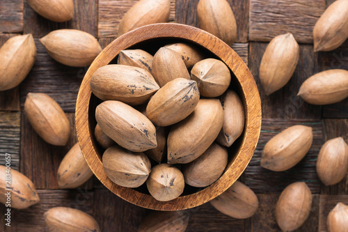 Cuadros en Lienzo  shelled pecan nuts raw in wooden bowl, top view.