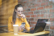 Girl sitting in a cafe, having breakfast and using her laptop
