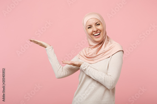 Cuadros en Lienzo Cheerful smiling young arabian muslim woman in hijab light clothes posing isolated on pink background in studio
