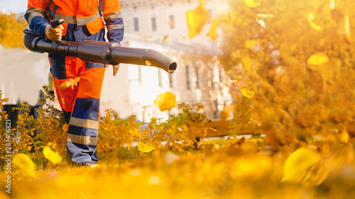Male worker removes leaf blower leaves lawn of garden Autumn Wallpaper Mural