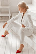 canvas print picture - Elegant blonde businesswoman in a white smart suit and red shoes sitting on white wooden stairs