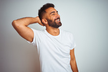Young Indian Man Wearing T-shirt Standing Over Isolated White Background Smiling Confident Touching Hair With Hand Up Gesture, Posing Attractive And Fashionable