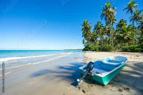 Foto  Small boat landed on the shore of a rustic beach on a remote island off the coas