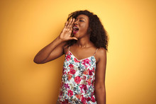 African American Woman Wearing Floral Summer T-shirt Over Isolated Yellow Background Shouting And Screaming Loud To Side With Hand On Mouth. Communication Concept.