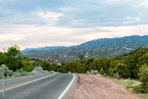 Fototapeta premium Zachód słońca na Bishops Lodge Road w Santa Fe w Nowym Meksyku z różowym światłem słonecznym na zielonych roślinach i drogą do osiedla Tesuque