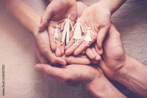 Obraz Adult and children hands holding paper family cutout, family home, adoption foster care, homeless charity,social distancing,  family mental health, Autism support, domestic violence, trust - fototapety do salonu