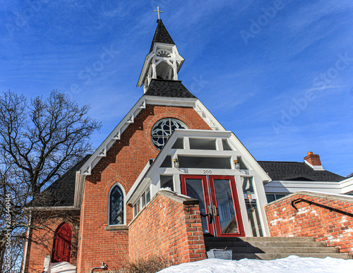 Orange brick church in rural midwest. Red doors, white trim & steeple topped with a cross. Large tree without leaves and blue sky.